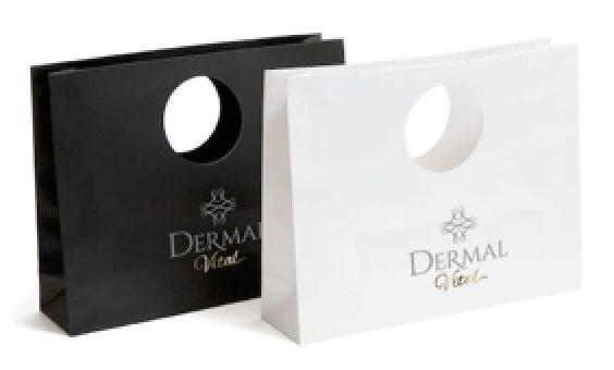 Zwei Tragetaschen mit dem Firmenlogo von Dermal Vital