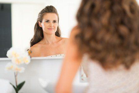 Lächelnde Frau nach einer Wimpernverlängerung betrachtet sich im Spiegel.