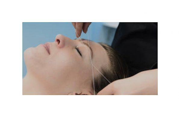 Fadenzupftechnik der Augenbrauen bei einer Frau