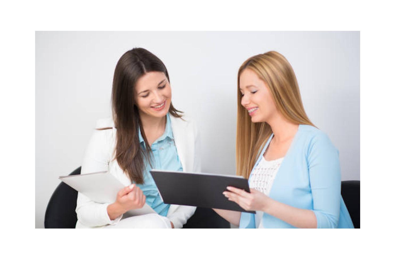 Zwei junge Frauen im Beratungsgespräch vor der Wimpernverlängerung